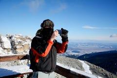 Homem novo que toma imagens com um smartphone de uma montanha bonita do inverno em Borovets, Bulgária Fotos de Stock Royalty Free