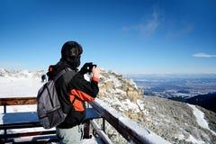 Homem novo que toma imagens de uma montanha bonita do inverno em Borovets, Bulgária Foto de Stock