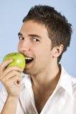 Homem novo que toma a mordida da maçã verde Foto de Stock