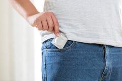 Homem novo que toma o preservativo fora do bolso nas calças de brim Foto de Stock