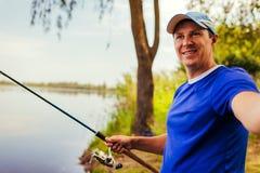 Homem novo que toma o selfie ao pescar no rio no por do sol Fiserman feliz fotos de stock royalty free