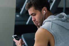 Homem novo que toma uma ruptura após seu exercício e que escuta a música em seu telefone Fotografia de Stock Royalty Free