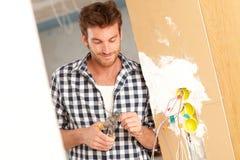 Homem novo que trabalha com eletricidade na casa nova Imagens de Stock Royalty Free