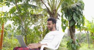 Homem novo que trabalha com laptop fora no hispânico tropical Guy Typing do jardim video estoque
