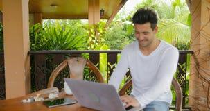 Homem novo que trabalha com o laptop no terraço Guy Typing Chatting Online de sorriso vídeos de arquivo
