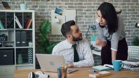 Homem novo que trabalha com o portátil que fala então à mulher bonita do colega de trabalho no escritório vídeos de arquivo