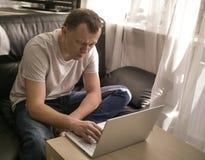 Homem novo que trabalha com o port?til que senta-se em casa perto da janela imagens de stock royalty free