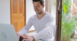 Homem novo que trabalha com a tabela de assento em casa Guy Typing de sorriso do laptop video estoque