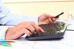 Homem novo que trabalha no computador no escritório Imagens de Stock Royalty Free