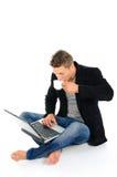 Homem novo que trabalha no portátil e no café bebendo foto de stock royalty free