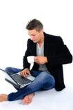 Homem novo que trabalha no portátil e no café bebendo foto de stock