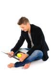 Homem novo que trabalha no portátil e que come a maçã imagens de stock