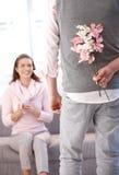 Homem novo que traz flores à mulher foto de stock
