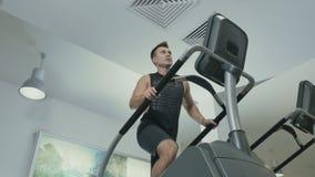 Homem novo que treina os pés que movem escadas no gym filme
