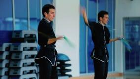 Homem novo que treina suas habilidades em mover a espada no gym filme