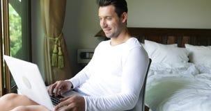 Homem novo que usa a janela de sorriso feliz de Guy Chatting Online Over Big do laptop com opinião tropical do jardim video estoque