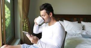 Homem novo que usa a janela de sorriso de Guy Chatting Online Over Big do café da bebida do tablet pc no quarto filme