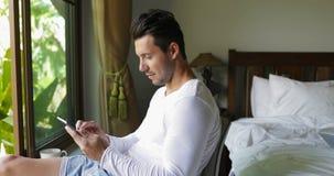 Homem novo que usa a janela de sorriso de Guy Chatting Online Over Big do tablet pc no quarto vídeos de arquivo
