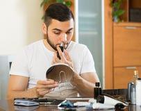Homem novo que usa o ajustador do cabelo imagem de stock royalty free