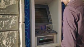 Homem novo que usa o ATM video estoque