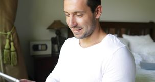 Homem novo que usa o café Guy Chatting Online In Bedroom de sorriso da bebida do tablet pc vídeos de arquivo