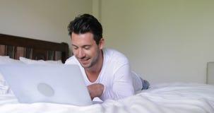 Homem novo que usa o laptop que encontra-se na manhã de sorriso feliz de Guy Chatting Online In Bedroom da cama video estoque