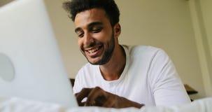 Homem novo que usa o laptop que encontra-se na manhã de sorriso feliz de Guy Chatting Online In Bedroom do hispânico da cama vídeos de arquivo