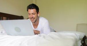 Homem novo que usa o laptop que tem a chamada video Guy Talking Lying On Bed do bate-papo na manhã do quarto filme