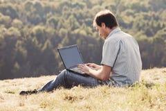 Homem novo que usa o portátil Imagem de Stock Royalty Free