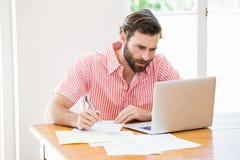 Homem novo que usa o portátil ao calcular contas Imagem de Stock