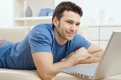 Homem novo que usa o portátil em casa fotografia de stock