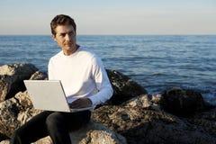 Homem novo que usa o portátil na praia Fotos de Stock