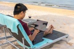Homem novo que usa o portátil na praia ensolarada na viagem do verão imagem de stock royalty free