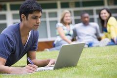 Homem novo que usa o portátil no gramado do terreno fotos de stock