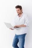 Homem novo que usa o portátil que está de sorriso Foto de Stock Royalty Free