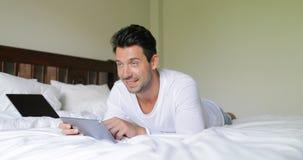 Homem novo que usa o tablet pc que encontra-se na manhã de sorriso de Guy Chatting Online In Bedroom da cama vídeos de arquivo