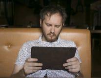 Homem novo que usa o tablet pc no café Imagens de Stock