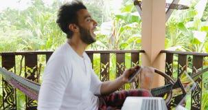 Homem novo que usa o tablet pc que ri no terraço, hispânico Guy Chatting Online filme