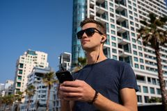 Homem novo que usa o telefone com auriculares Skyline da cidade no fundo fotos de stock royalty free