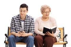 Homem novo que usa o telefone com o livro de leitura maduro da mulher Imagens de Stock Royalty Free