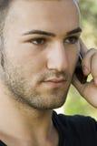 Homem novo que usa o telefone de pilha Fotografia de Stock