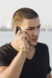 Homem novo que usa o telefone de pilha Imagem de Stock