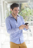Homem novo que usa o telefone esperto Fotografia de Stock