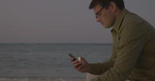 Homem novo que usa o telefone esperto pelo mar na noite video estoque