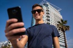 Homem novo que usa o telefone Skyline da cidade no fundo foto de stock royalty free