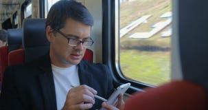 Homem novo que usa a pilha para consultar em linha no trem video estoque