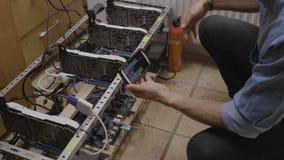 Homem novo que usa seu app do smartphone que verifica o processo do equipamento do cryptocurrency e o uso de mineração da energia vídeos de arquivo