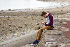 Homem novo que usa seu telefone celular na praia Imagens de Stock