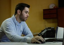 Homem novo que usa seus móbil, tabuleta, portátil e fones de ouvido fotos de stock
