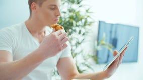 Homem novo que usa a tabuleta digital ao comer o café da manhã na tabela vídeos de arquivo